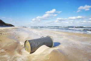 trash can on a beach environmental pollution conce PXFDJQM