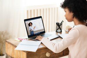 schoolgirl at laptop having online class with teac XZY9TTP